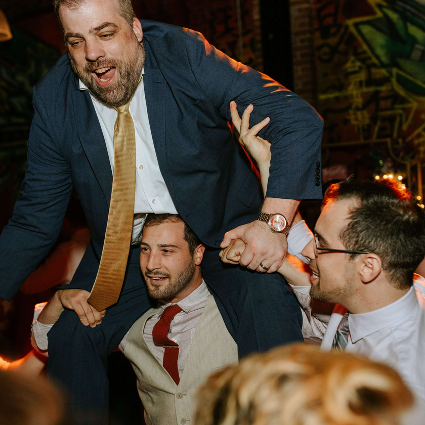 guy sits on shoulders of another guy at wedding