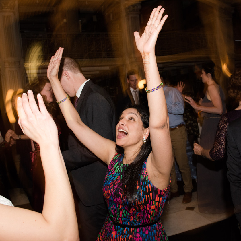 woman dancing with hands up at wedding