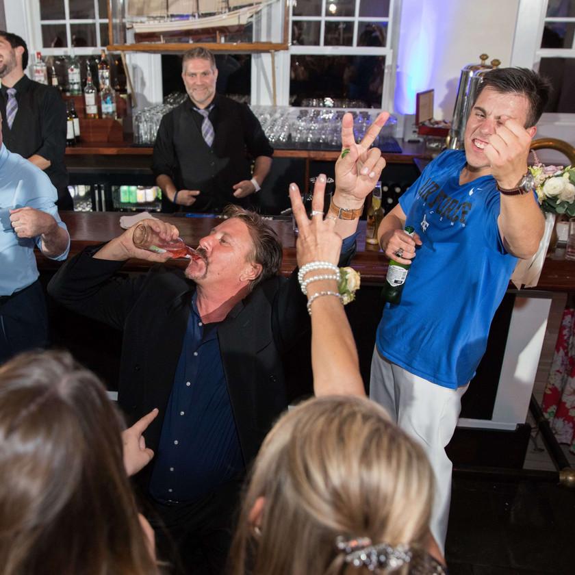 guy chugs beer at wedding