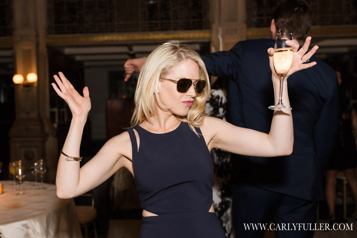woman in black dress and sunglasses dancing with hands up and glass of champagne