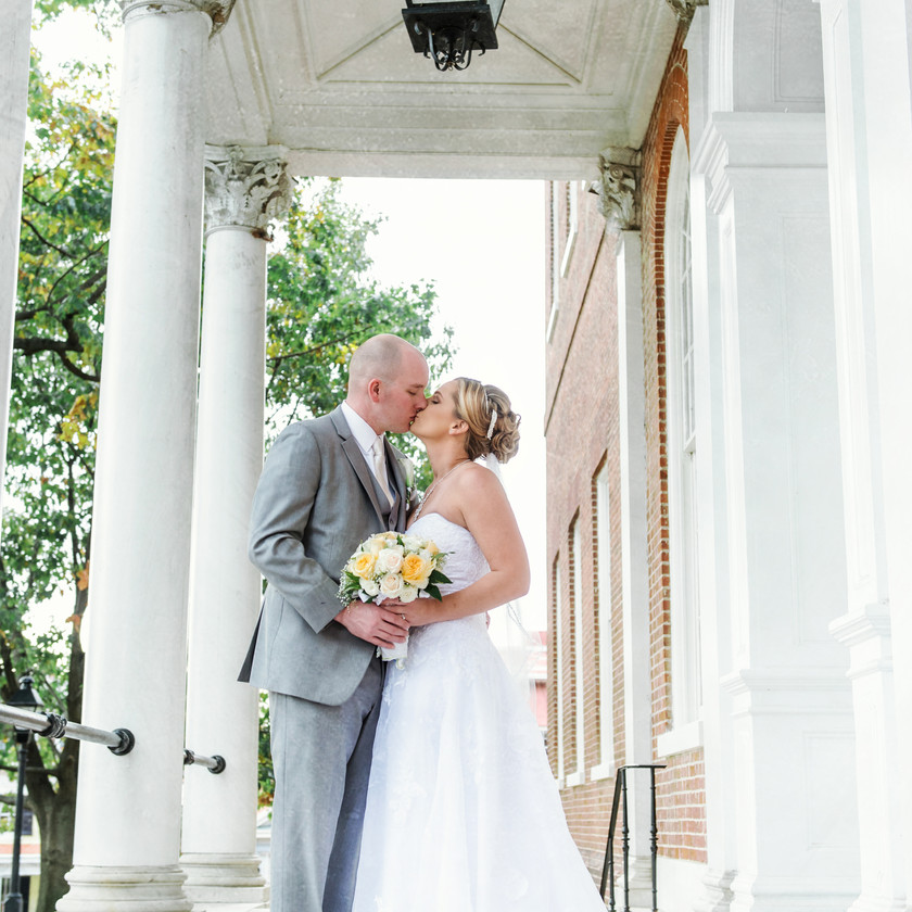 bride and groom kiss in front of building