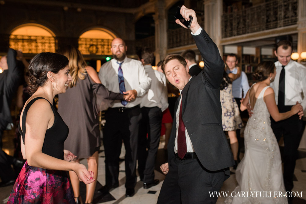 man dancing with hand up at wedding