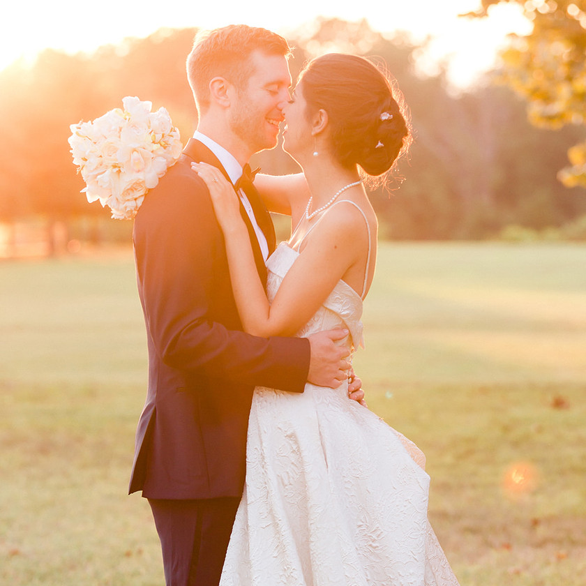 bride and groom kiss during sunset