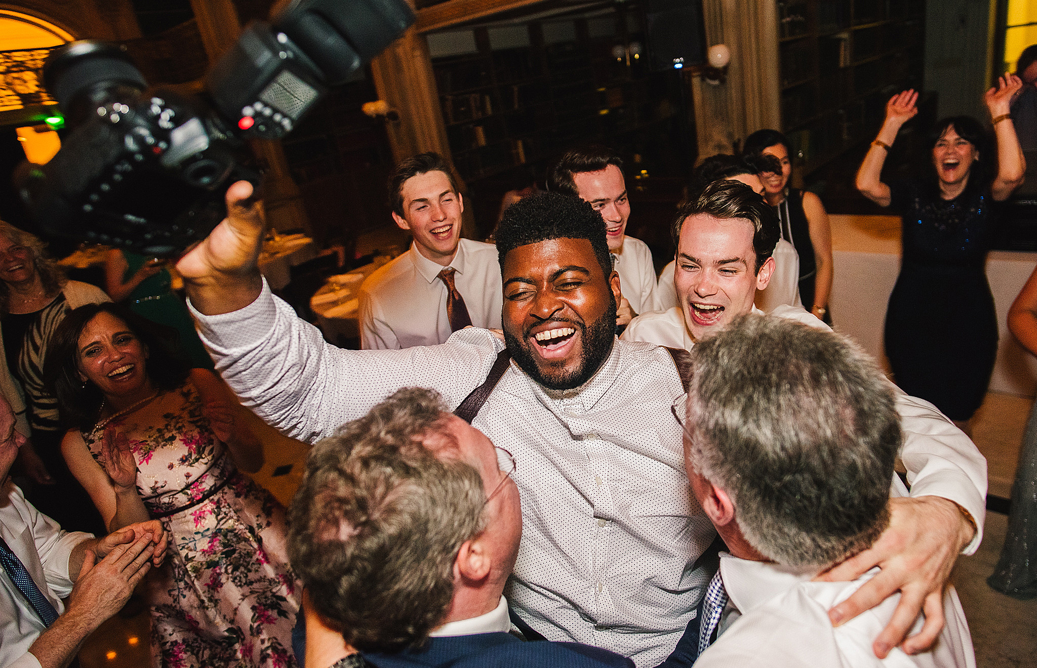 photographer dances with guests at wedding