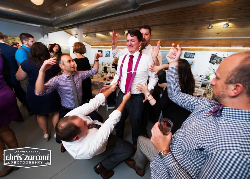 guy pulling on groom's suspenders while dancing