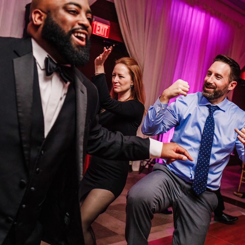 guy in blue shirt dancing at wedding with groom