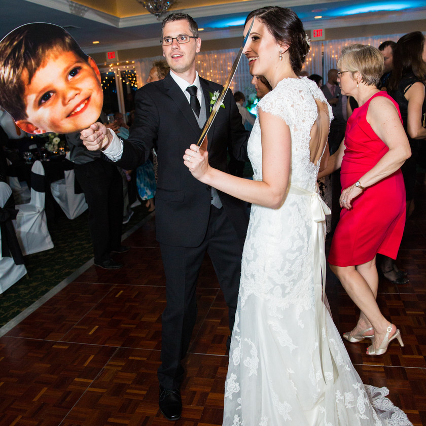 bride and groom with posters of their childhood faces dancing