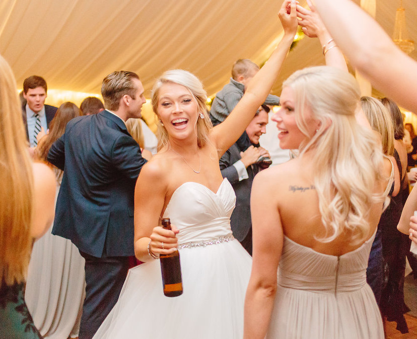 bride smiling and dancing with guests