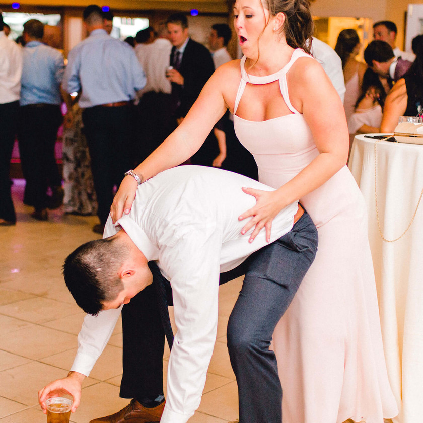 guy bending over while bridesmaid dances behind him