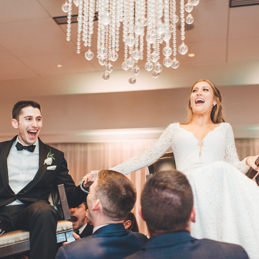 bride and groom up in chairs for hora