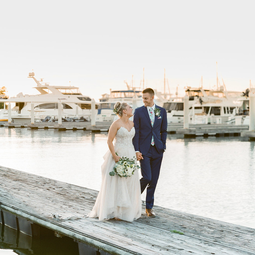 bride and groom walk on harbor dock by boats