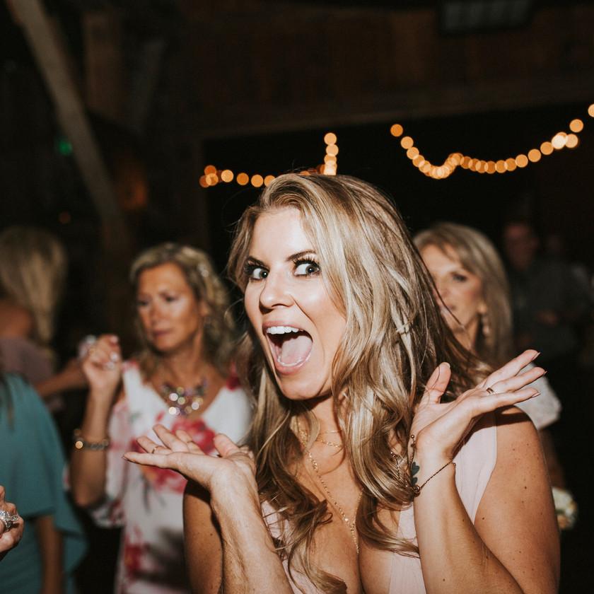 bridesmaid smiling at camera while dancing