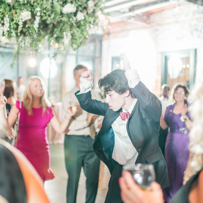 young man in bow tie dancing with hands up