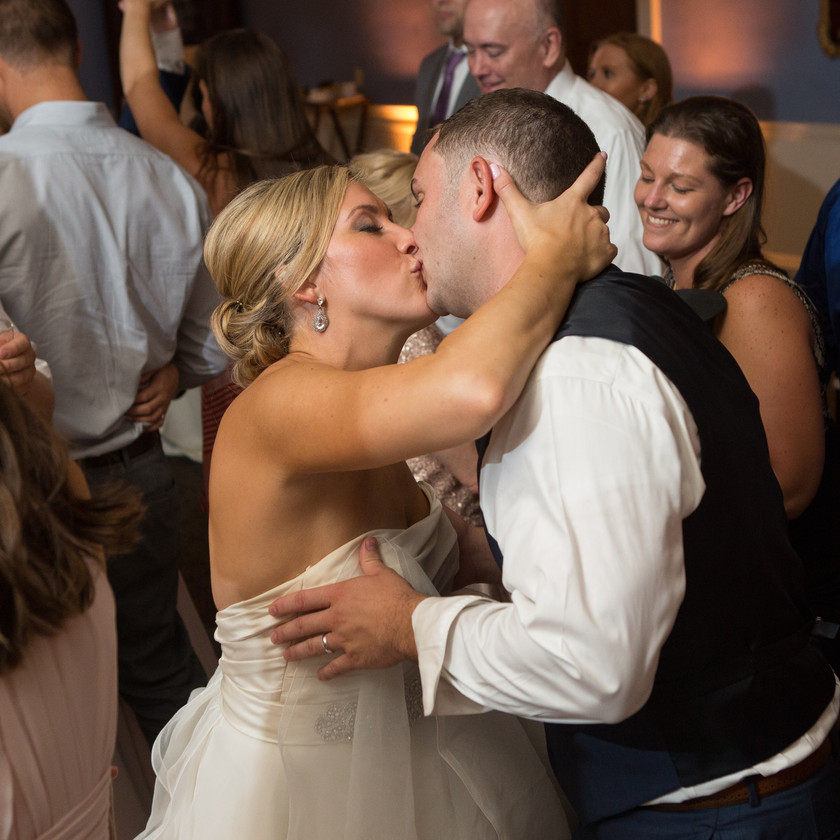 bride kisses groom while dancing