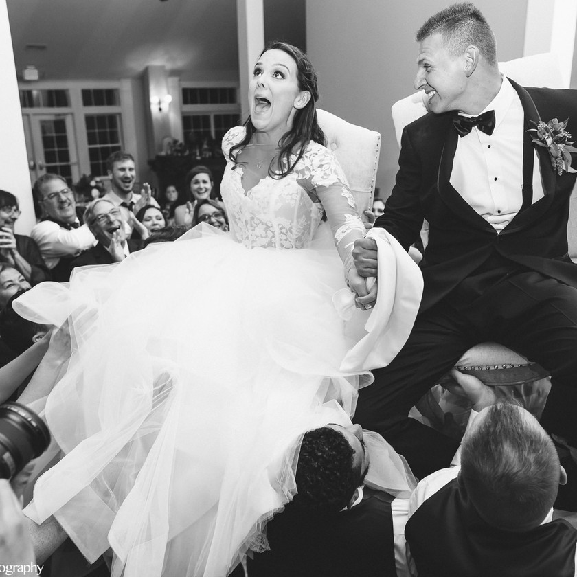 bride and groom up in chairs during hora