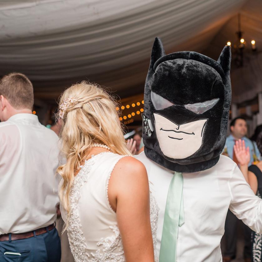 groom wears batman head while dancing with bride