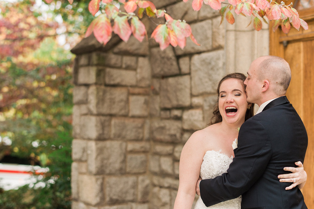 groom kissing bride on head while she laughs