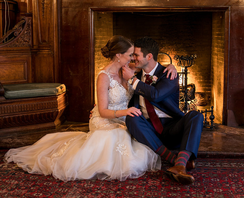 bride and groom about to kiss in front of fireplace