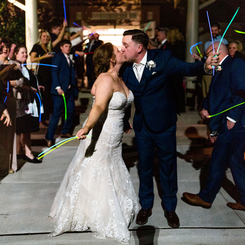 bride and groom kiss during glow stick exit