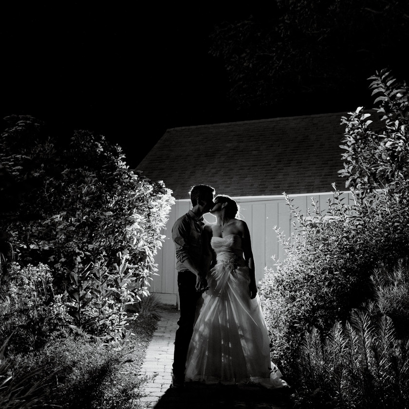 bride and groom kiss at night in garden