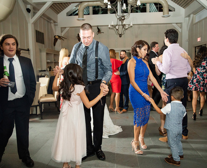 man and woman slow dance with small kids at wedding