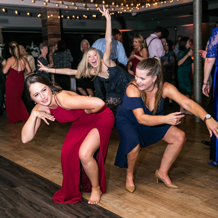 women bend over dancing at wedding