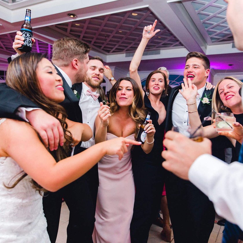 wedding party gathers arm in arm to dance