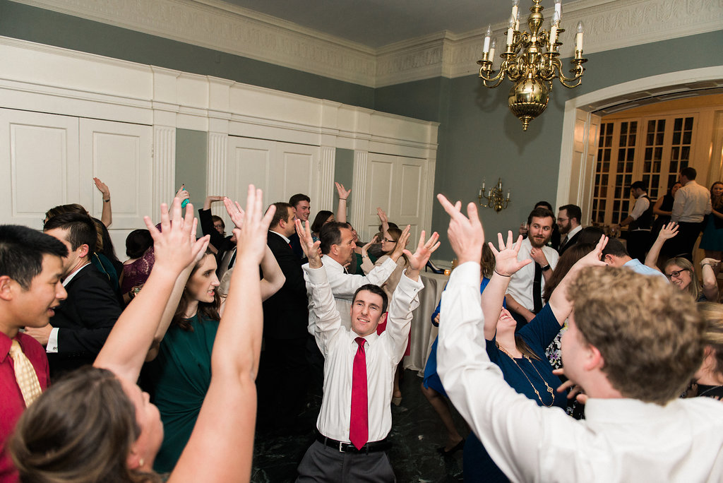 all guests have hands up while dancing at wedding