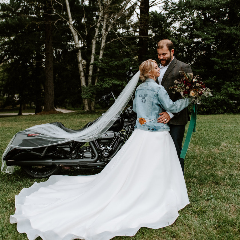 bride and groom pose in front of harley motorcycle