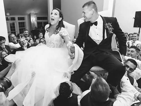 bride and groom hora chairs.webp