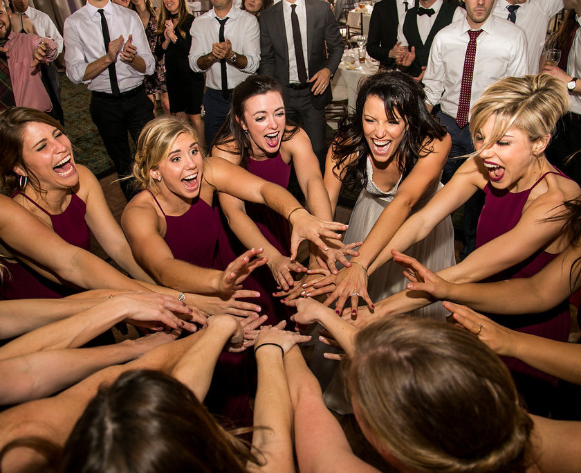 bride and bridesmaids put hands in together
