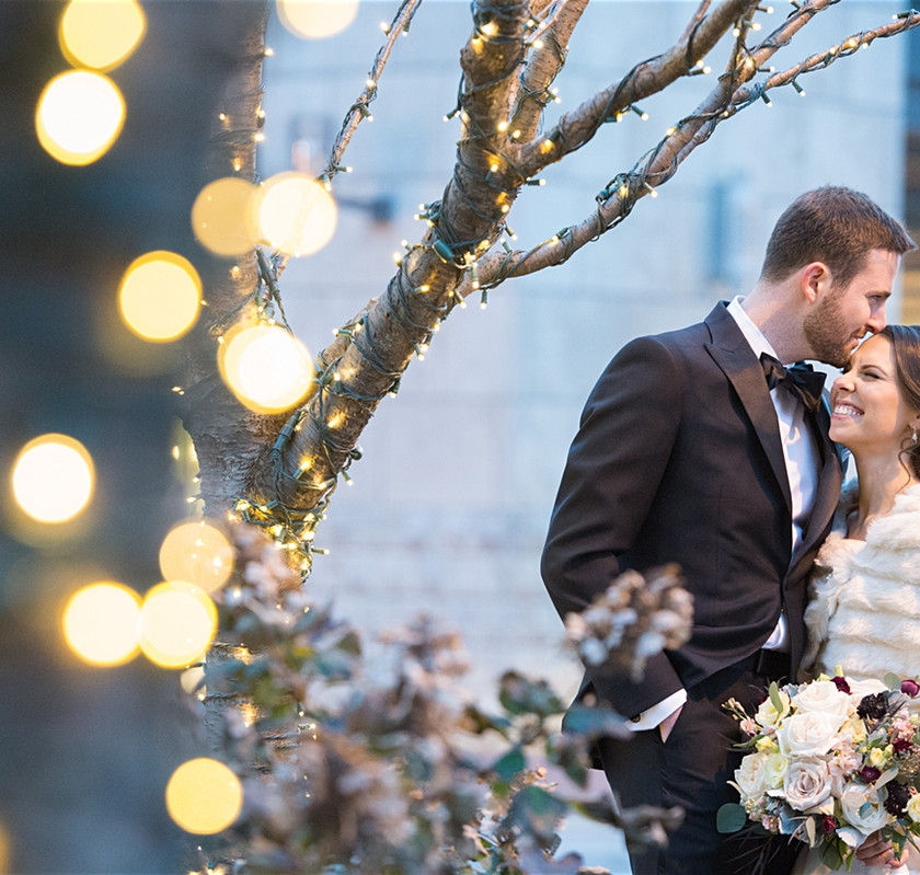 bride and groom pose in front of tree
