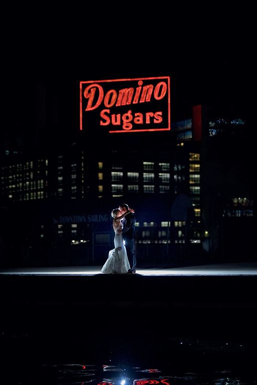 bride and groom kiss with domino sugar sign in background