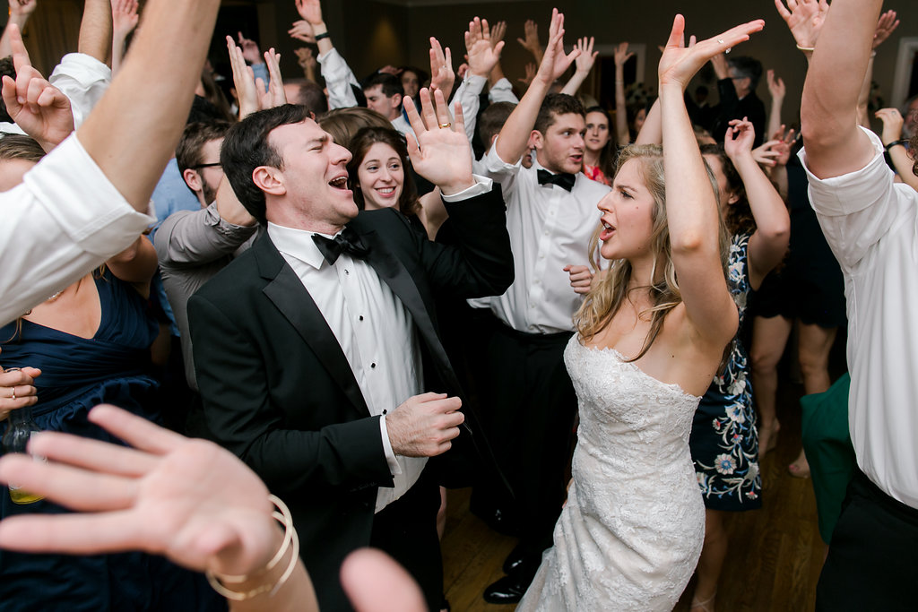bride and groom dancing and singing with hands up
