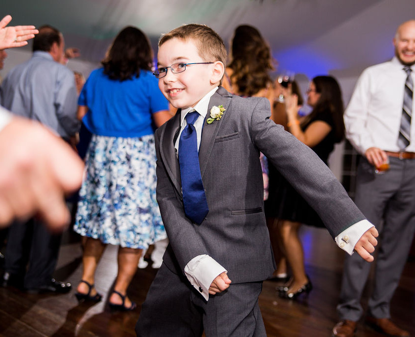 young boy in suit dances the floss