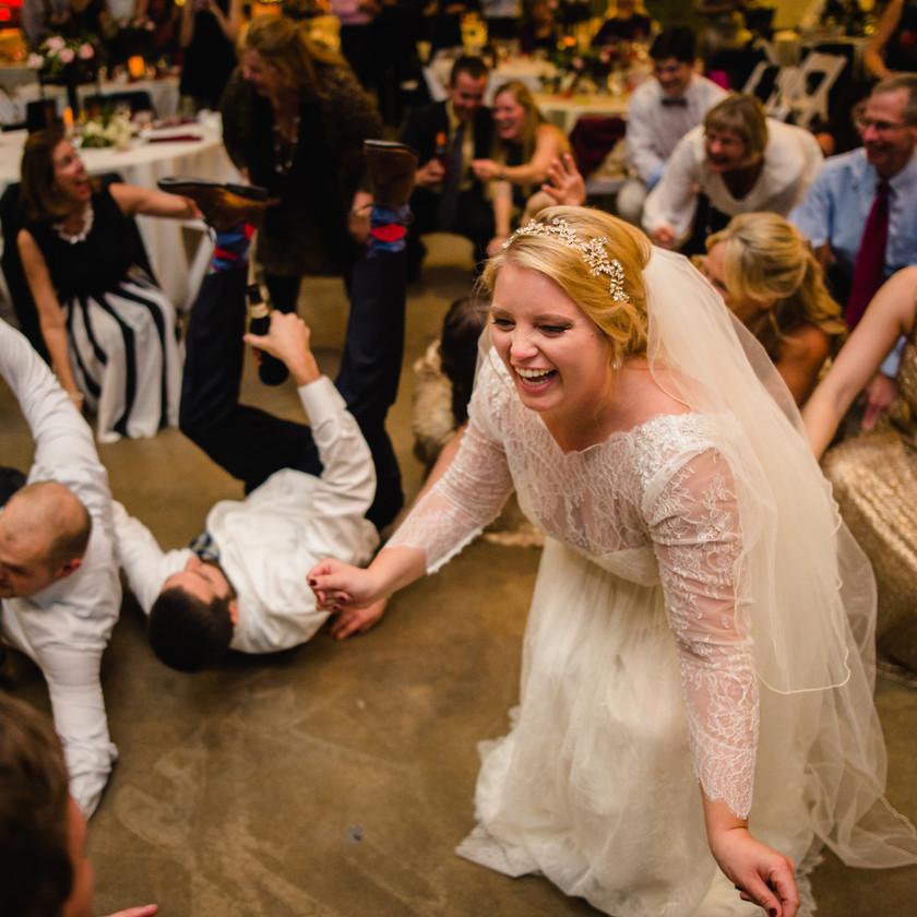 bride laughing while guests get low on dance floor