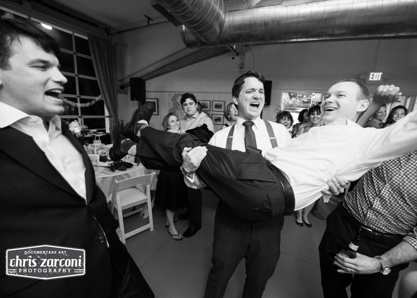 groom carrying guy on dance floor
