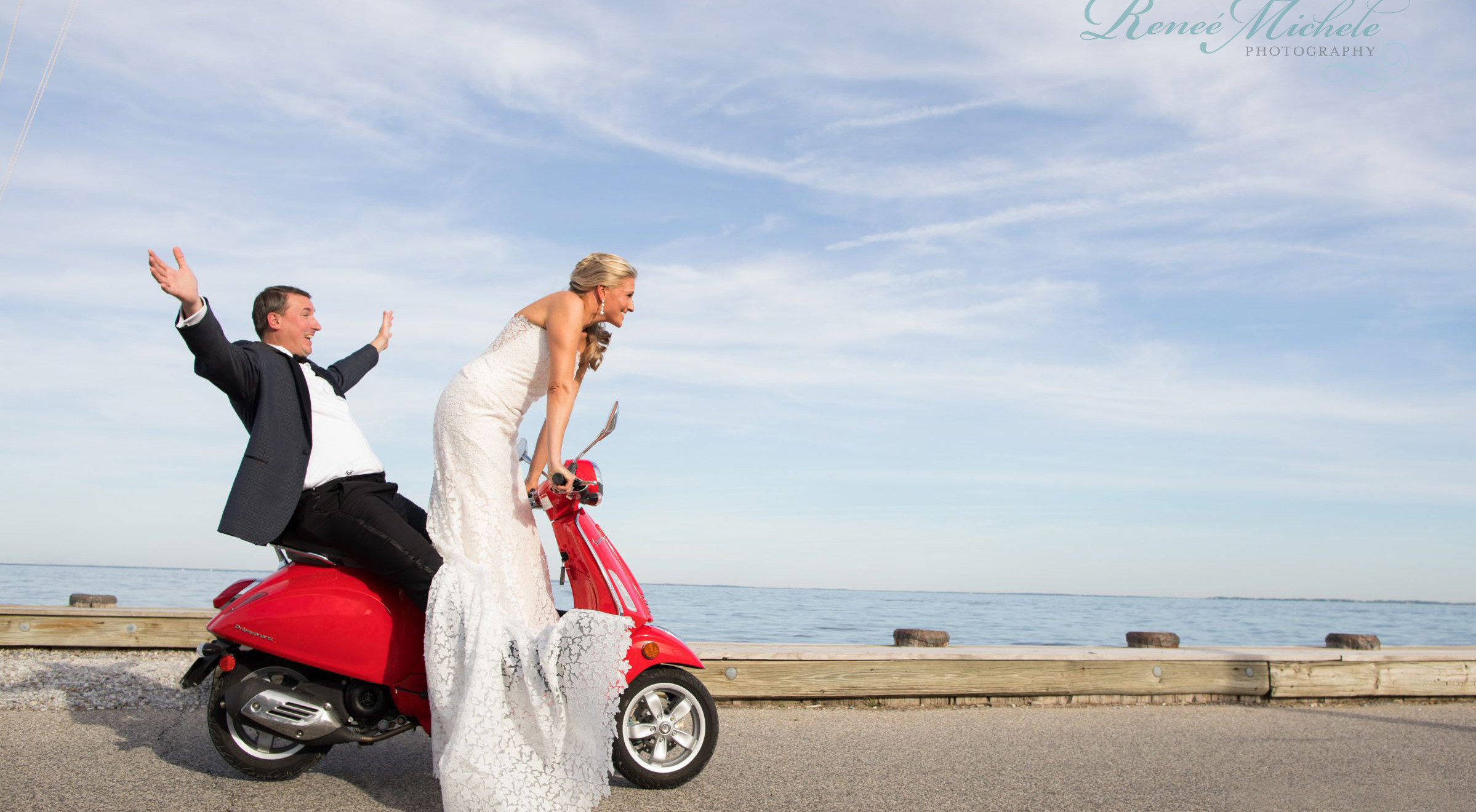 Bride and groom riding a red scooter