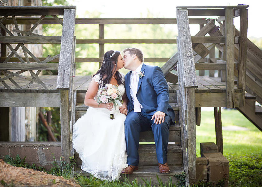 bride and groom kiss on porch