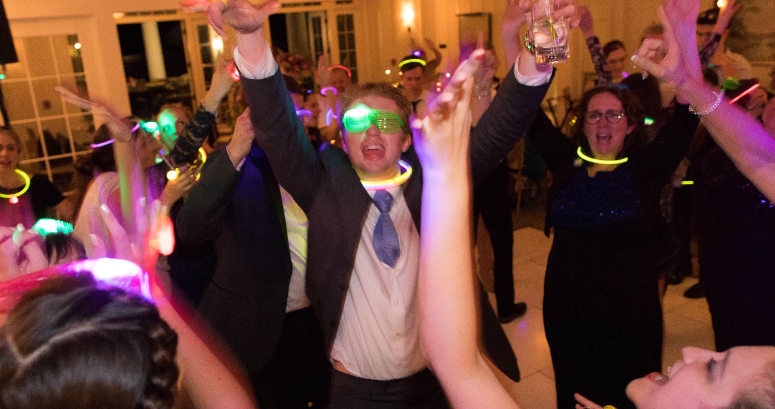 wedding guests dance with hands up and glow sticks