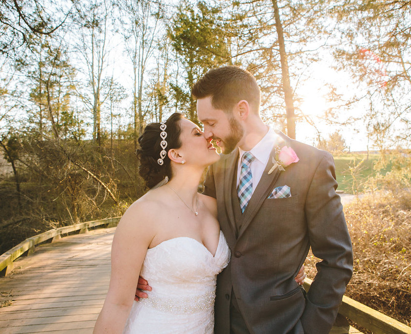 bride and groom about to kiss on wooden bridge