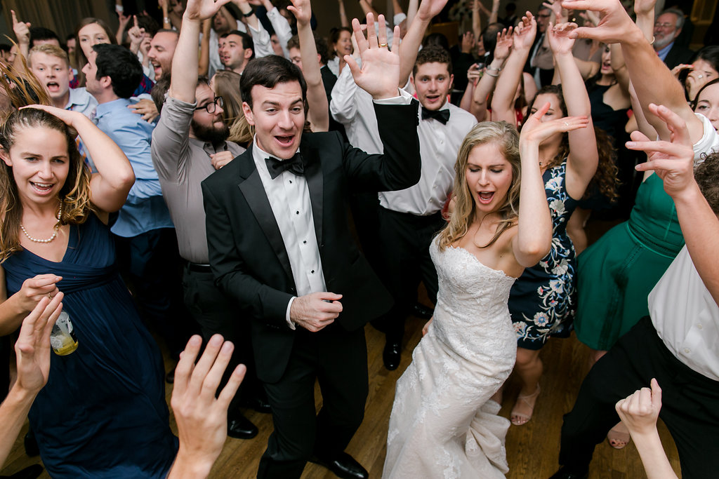 wedding guests with hands up while dancing