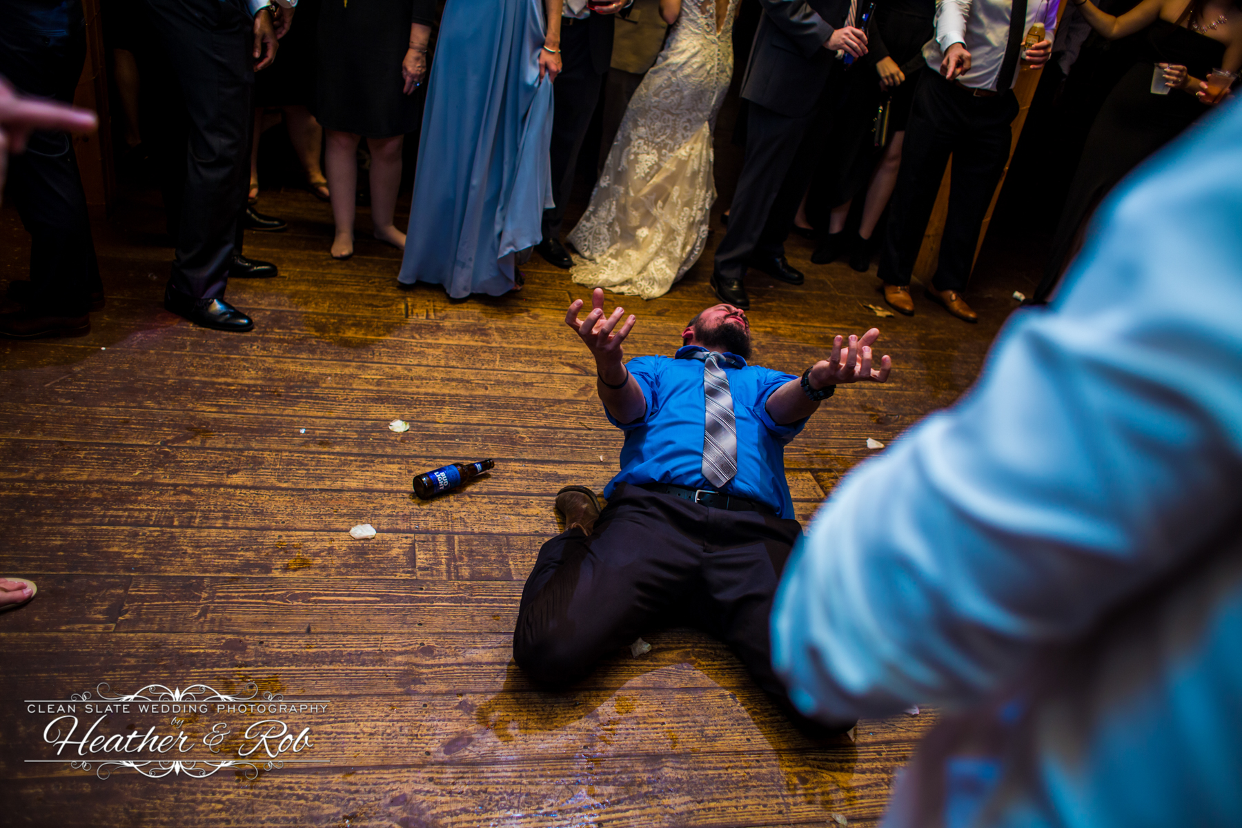 guy in blue shirt laying on the dance floor singing