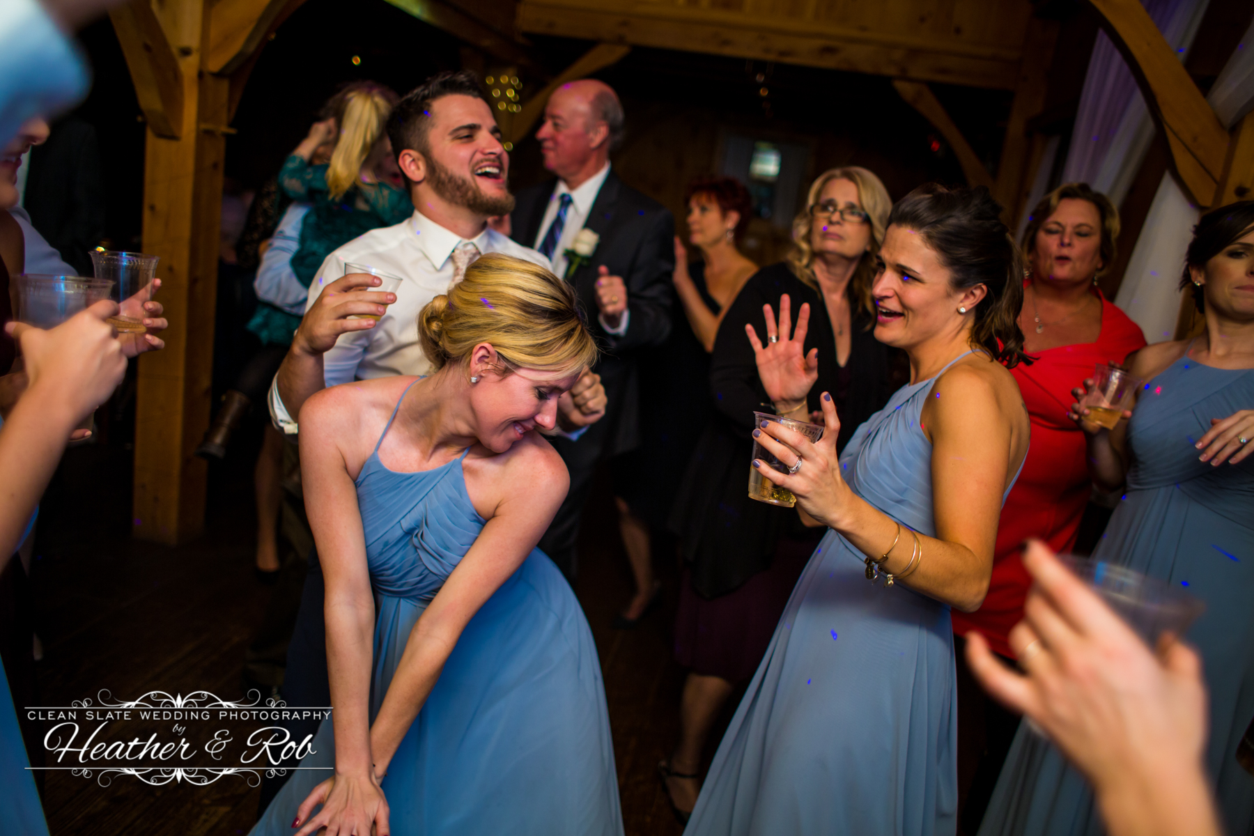 bridesmaid in blue dress dancing bent over at wedding
