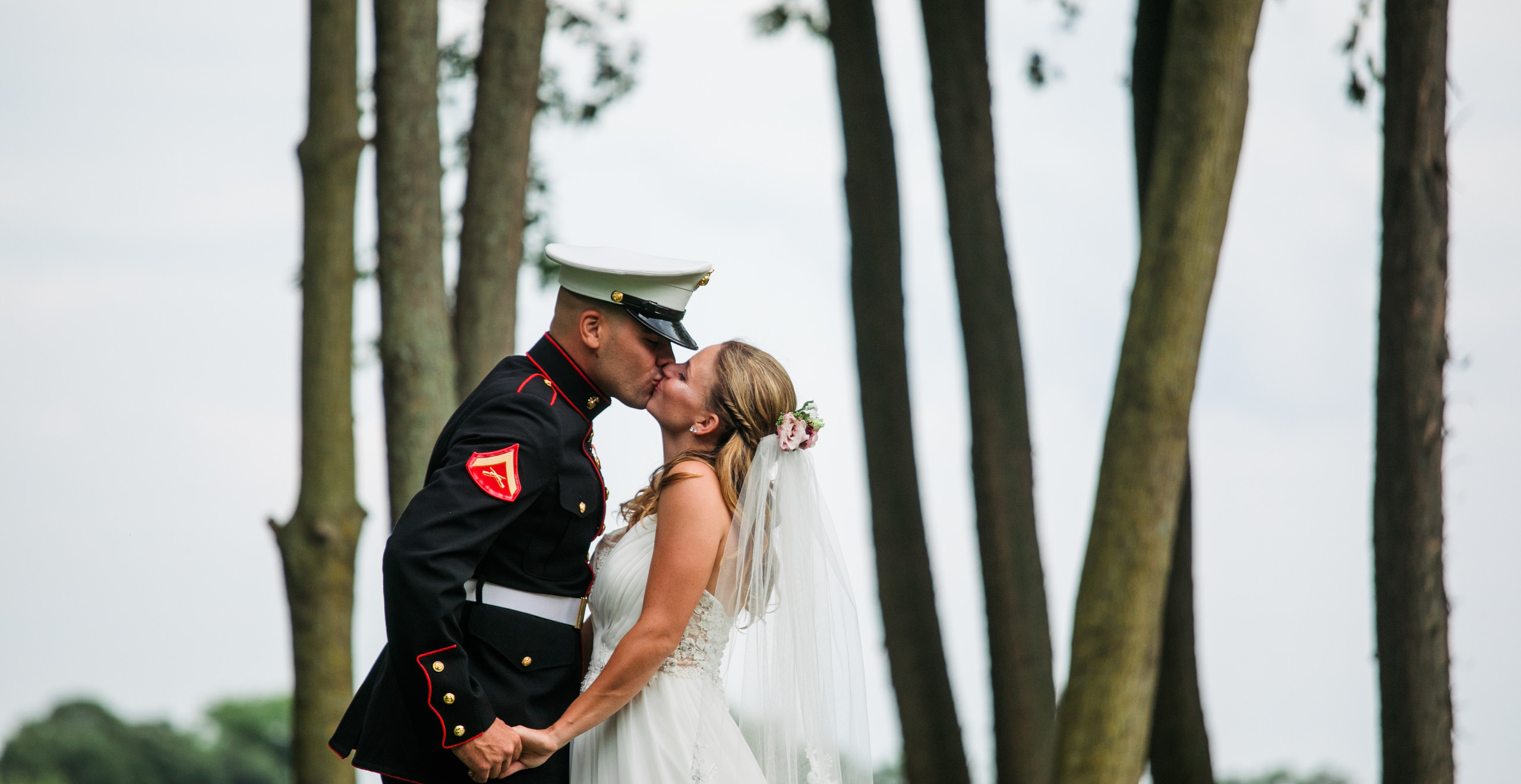 bride and marine kiss underneath the trees
