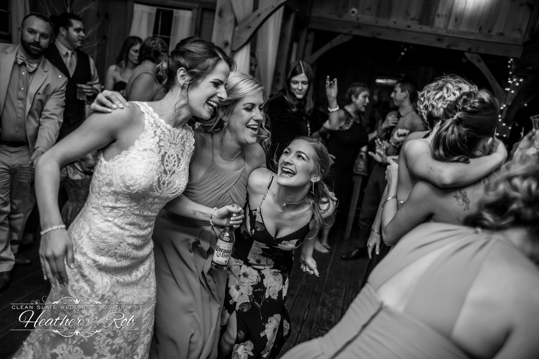 bride and friends laughing on the dance floor at wedding