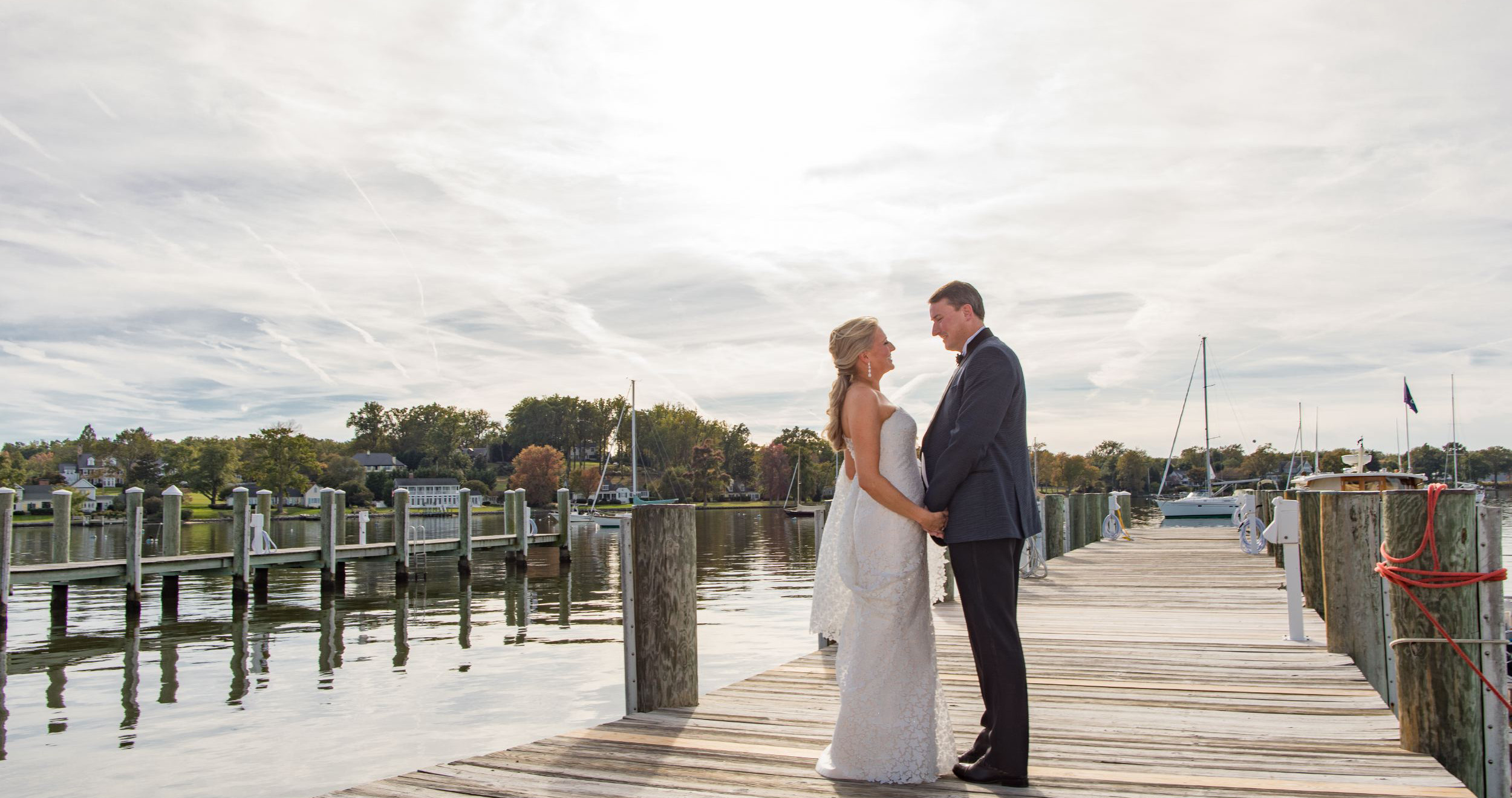 bride and groom standing on on pier