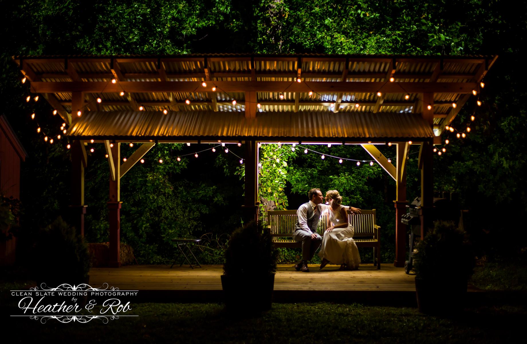 bride and groom sit under pergola at night