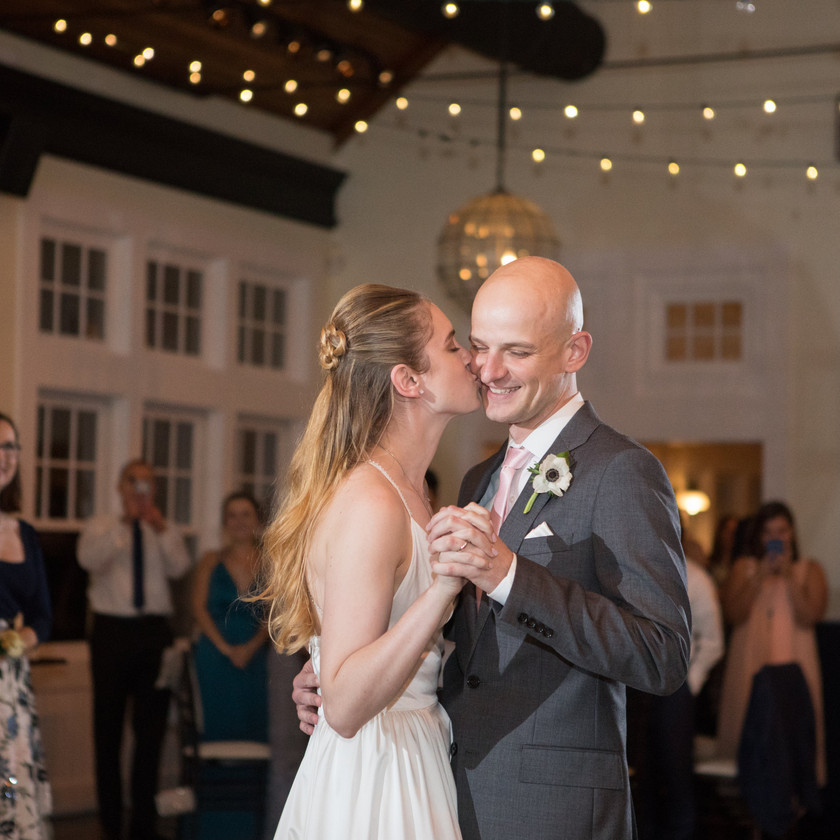bride kisses groom's cheek during first dance