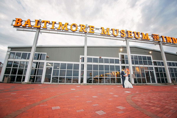 bride and groom stand in front of baltimore museum of industry sign
